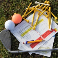 Golf scorecards, tees and putter on grass